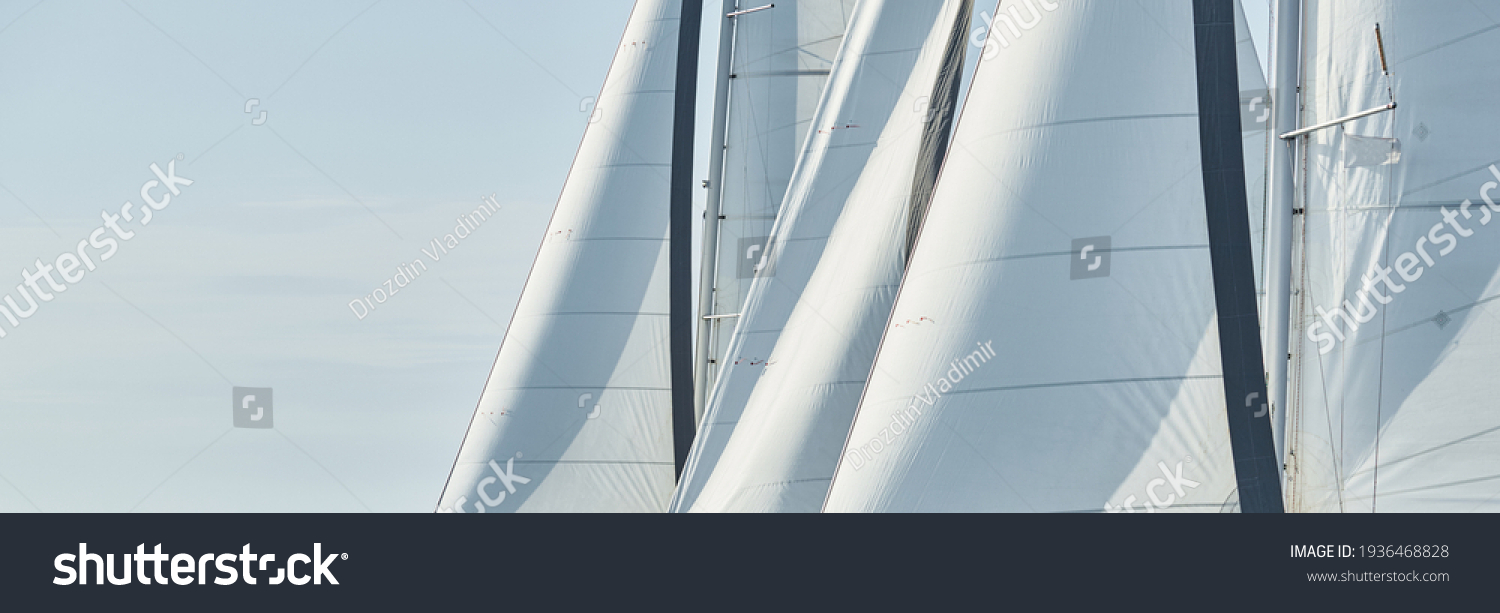 Some sails of white color, sailboats compete in a sailing regatta at sunset, sailing race #1936468828