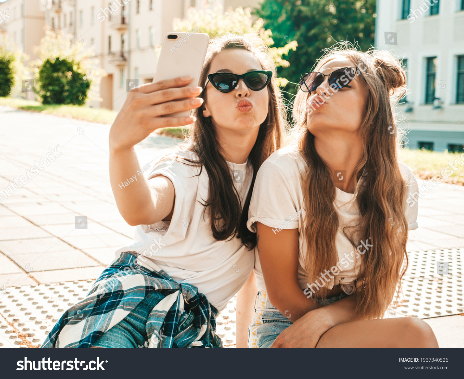 Portrait of two young beautiful smiling hipster women in trendy summer white t-shirt clothes.Sexy carefree women posing on street background. Positive models having fun, hugging and taking selfie #1937340526