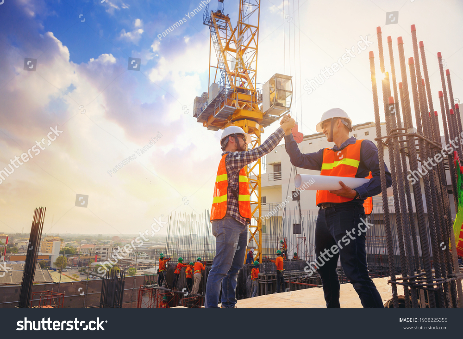 Architect and engineer construction workers shaking hands while working at outdoors construction site. Building construction collaboration concept #1938225355