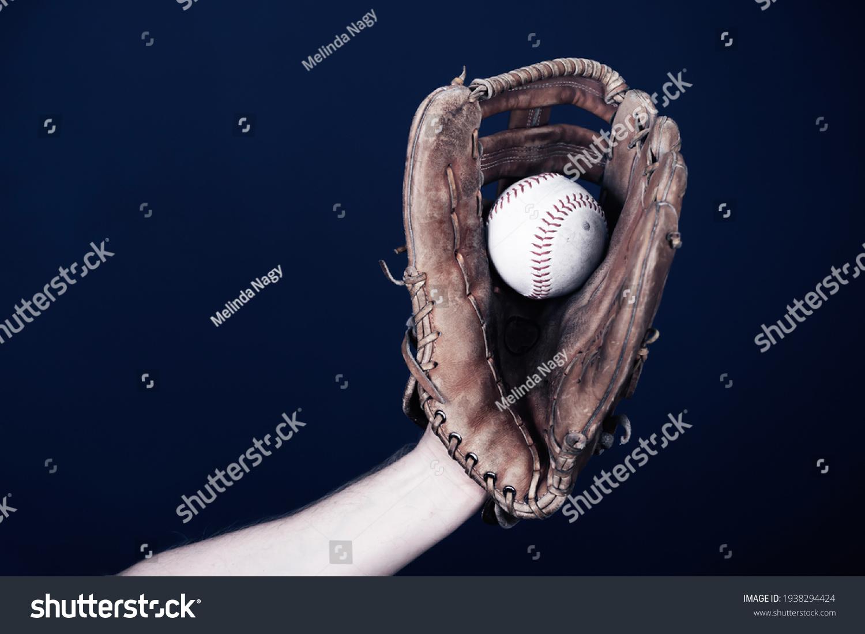 Close up image of an old used baseball and baseball glove. #1938294424