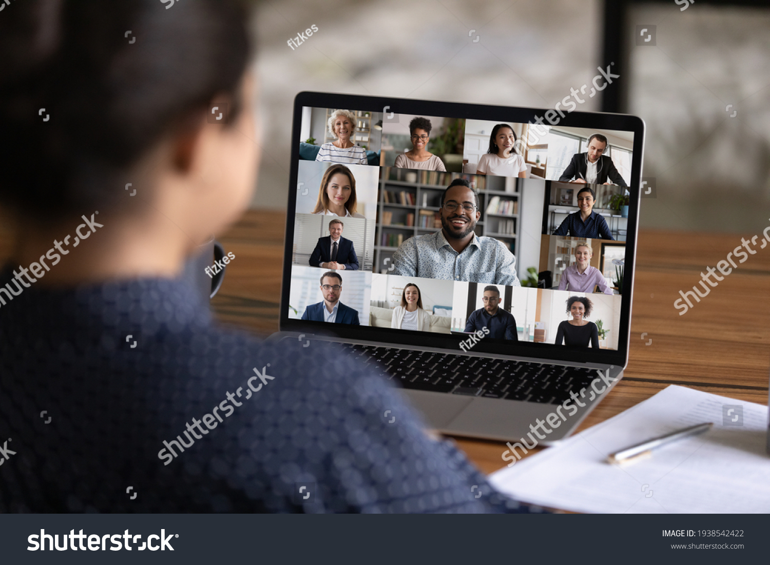 Over shoulder view of female worker have webcam digital virtual conference with diverse multiethnic colleagues. Woman speak talk on video call with multiracial businesspeople. Online meeting concept. #1938542422