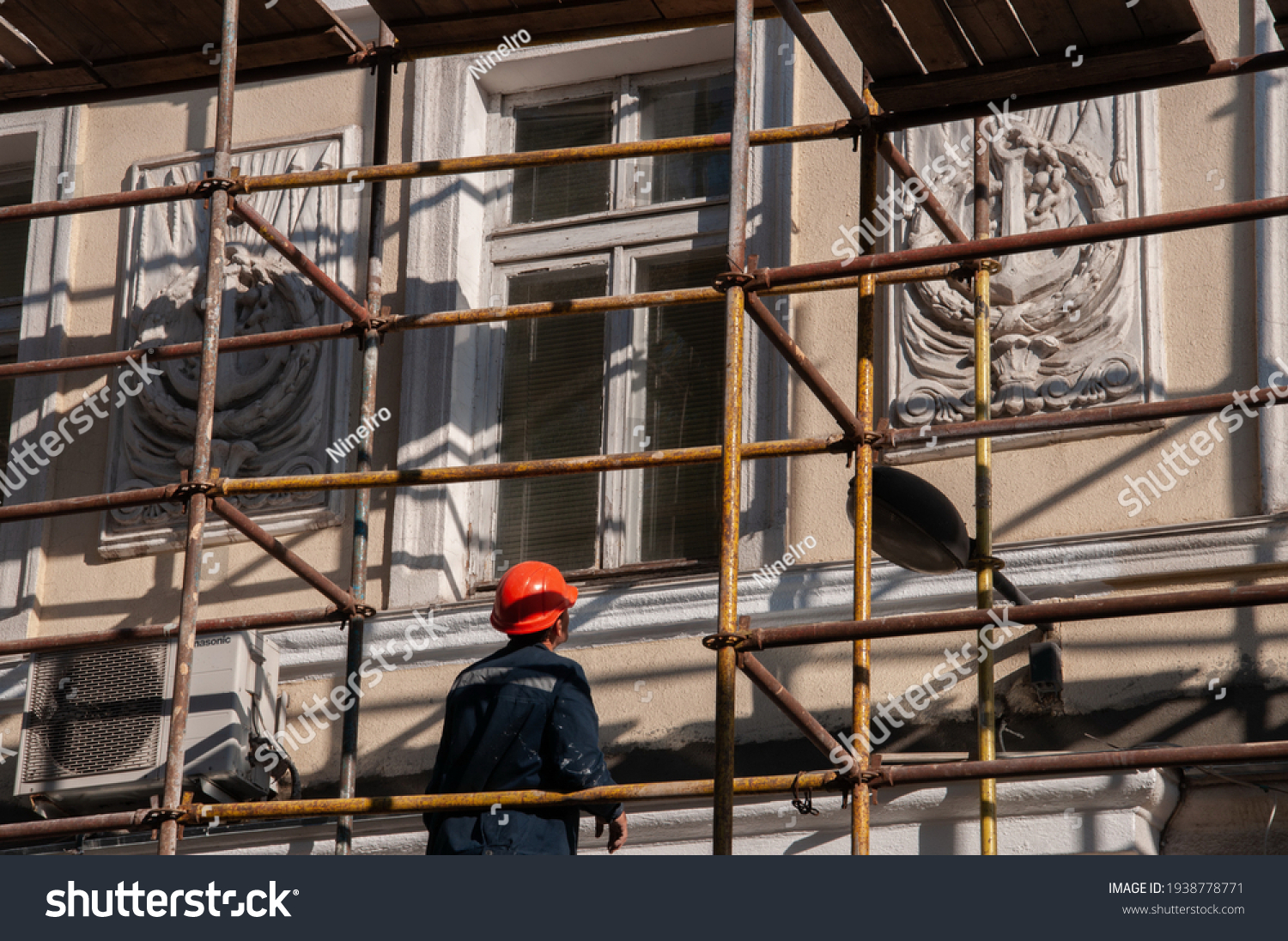 Man builder in orange construction helmet working from scaffolding to renovate historic building wall with ornate sculptural relievo details. Historic building restoration in progress #1938778771
