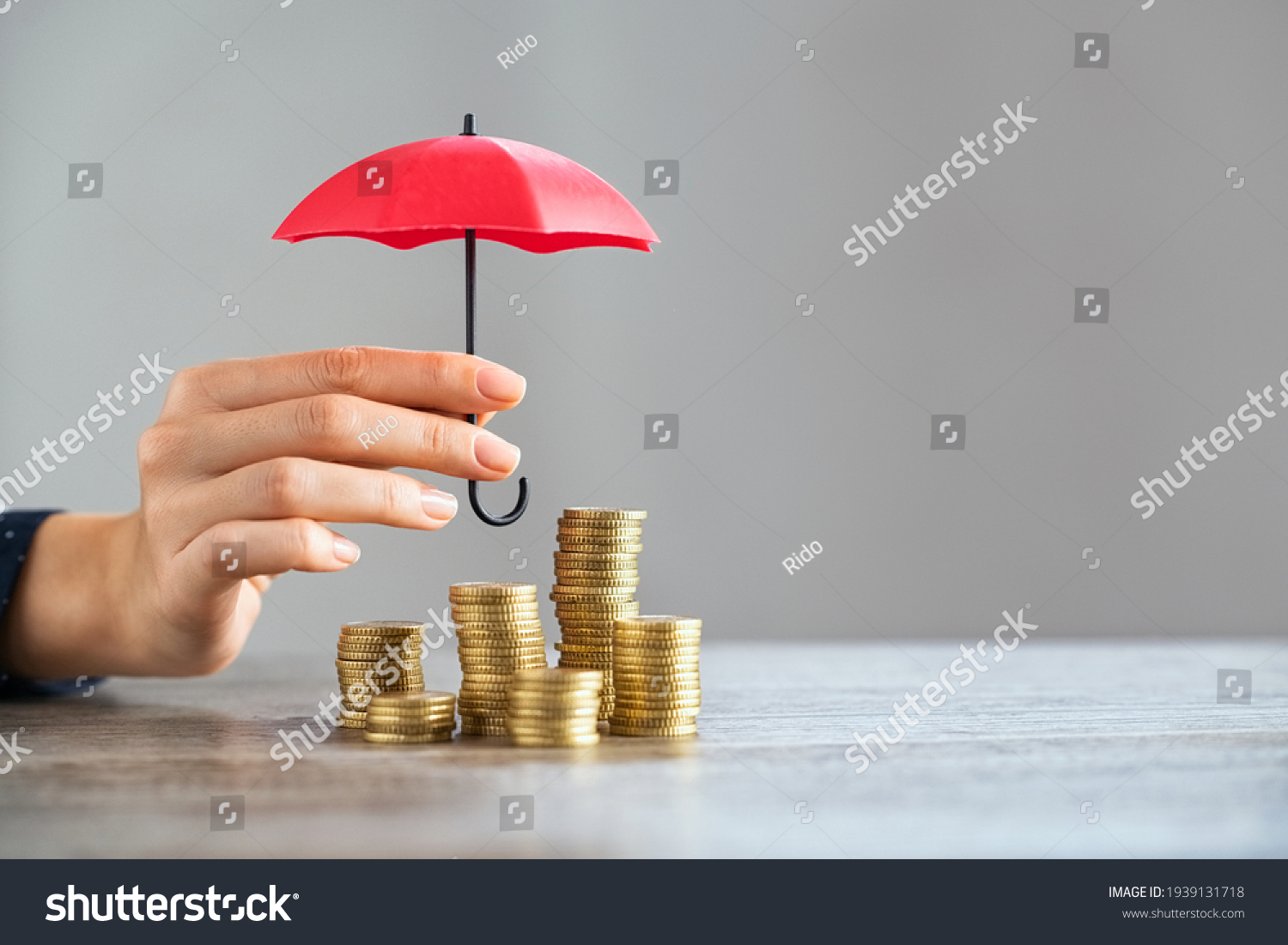 Young woman hand holding small red umbrella over pile of coins on table. Close up of stack of coins with female hands holding umbrella for protection. Financial safety and investment concept.   #1939131718