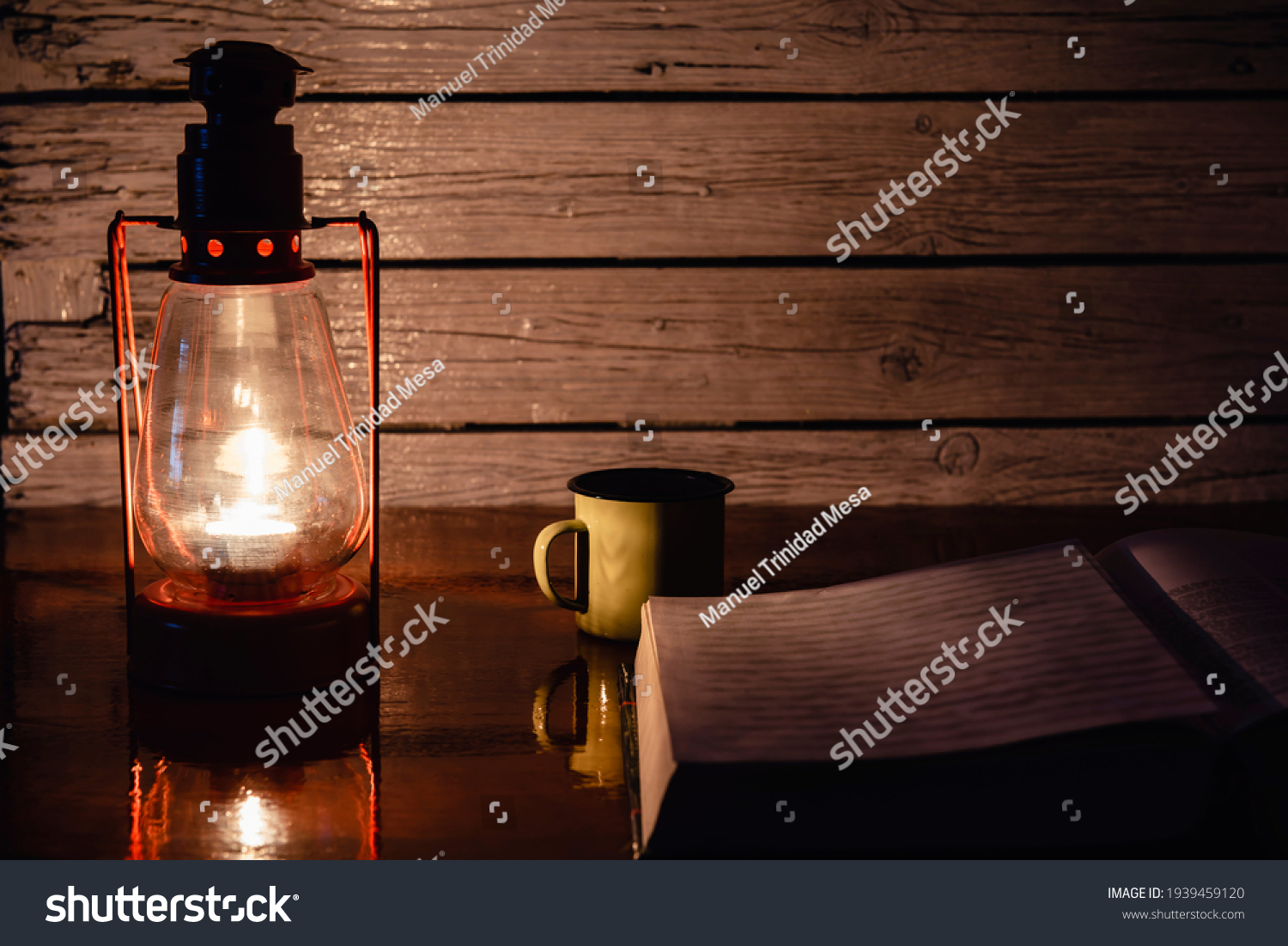 An open book and a cup of coffee in the light of a chandelier at night.