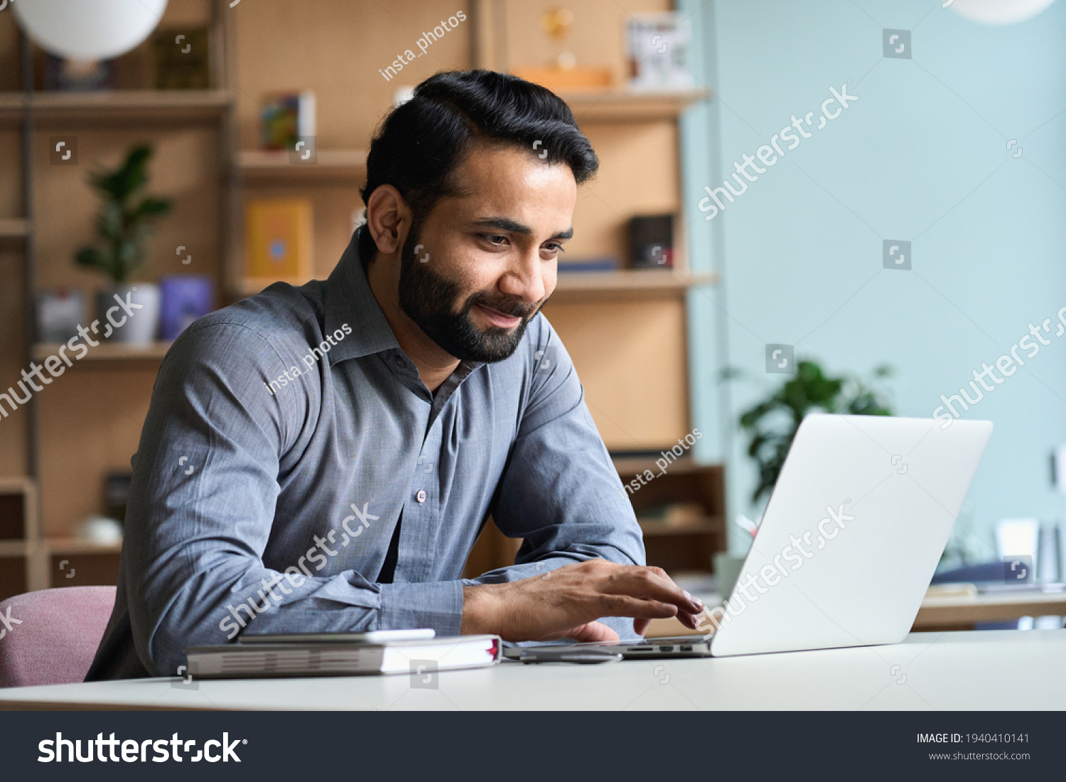 Smiling indian business man working on laptop at home office. Young indian student or remote teacher using computer remote studying, virtual training, watching online education webinar at home office. #1940410141