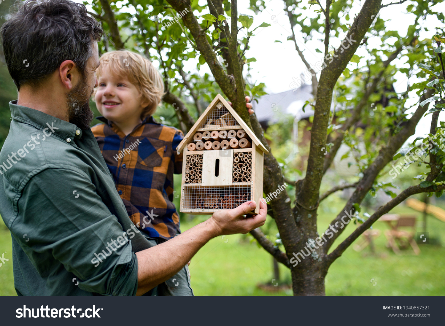 Small boy with father holding bug and insect hotel in garden, sustainable lifestyle. #1940857321