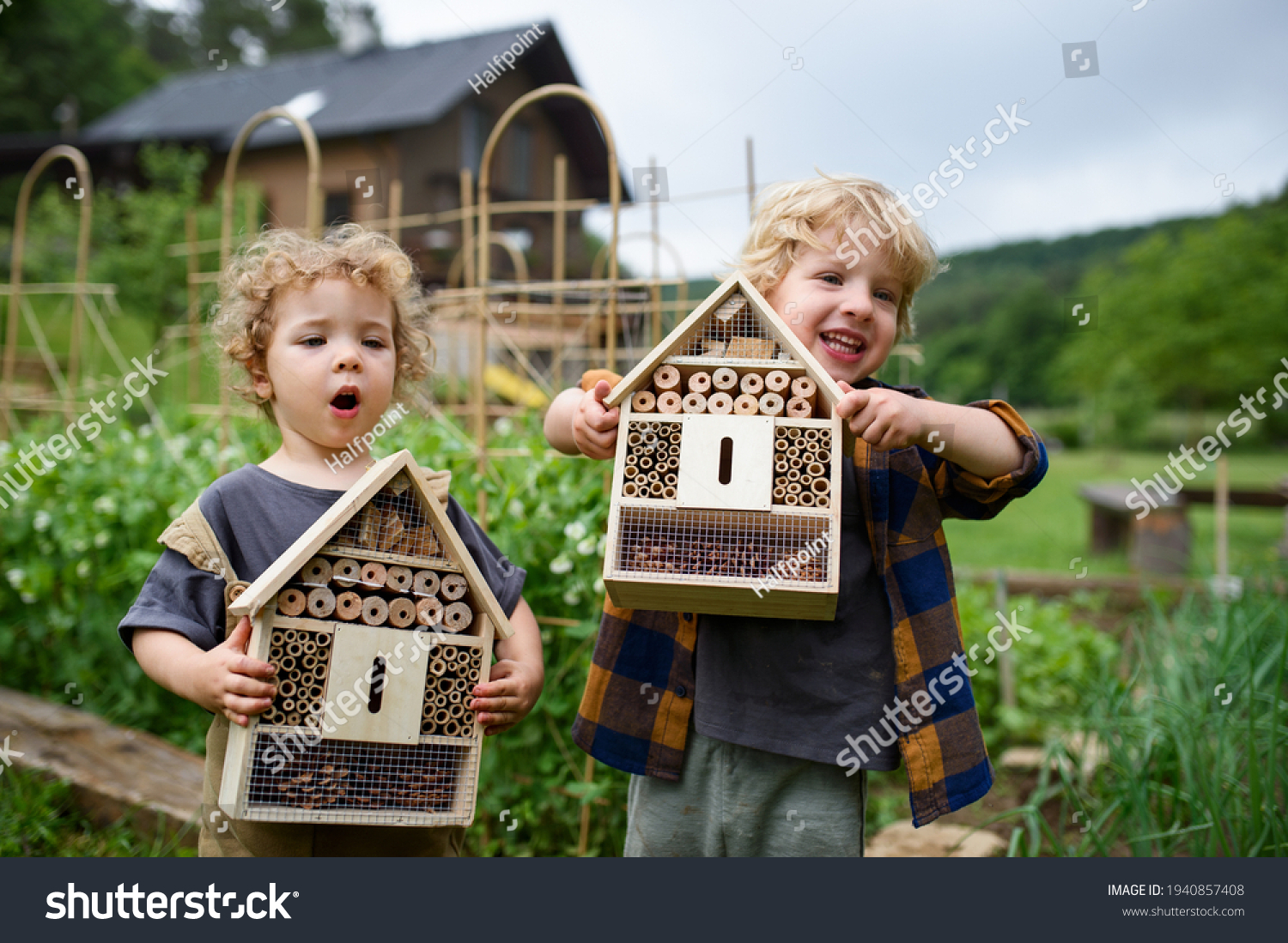Small boy and girl holding bug and insect hotel in garden, sustainable lifestyle. #1940857408