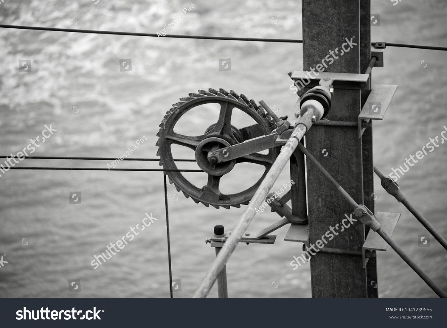 Closeup view of a gear keeping tension of electric wires in the railway electrification system. Irish railroad infrastructure with the Irish Sea in the background. Black and white industrial photo.