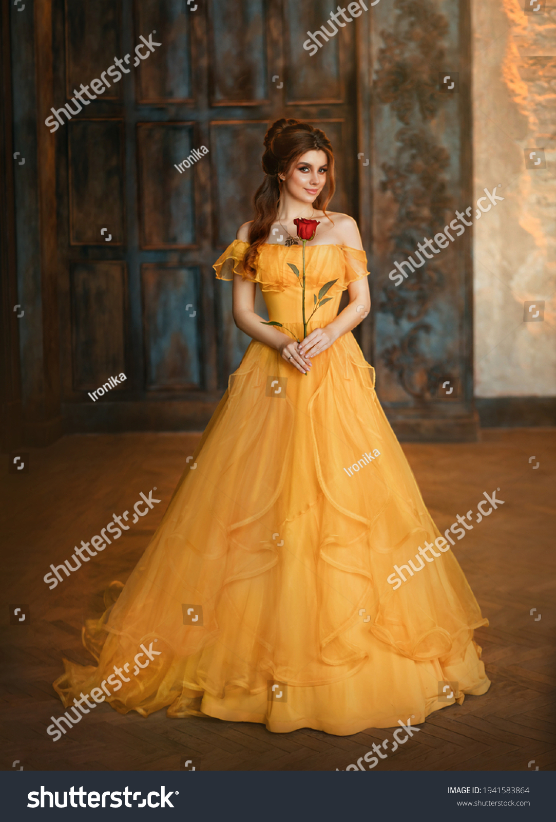 Girl beauty fantasy princess in yellow long historical, medieval silk dress holding flower red rose in her hands. Background of old gothic castle room. Fairy tale bewitched queen. Happy woman smiles. #1941583864