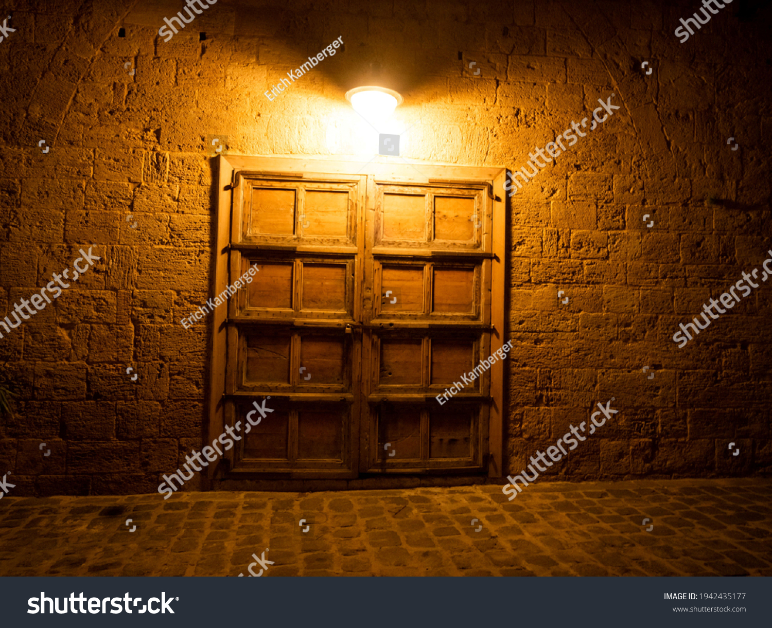 closed wooden door to a stone house at night illuminated by an electrical lamp in the city of Batroun Lebanon