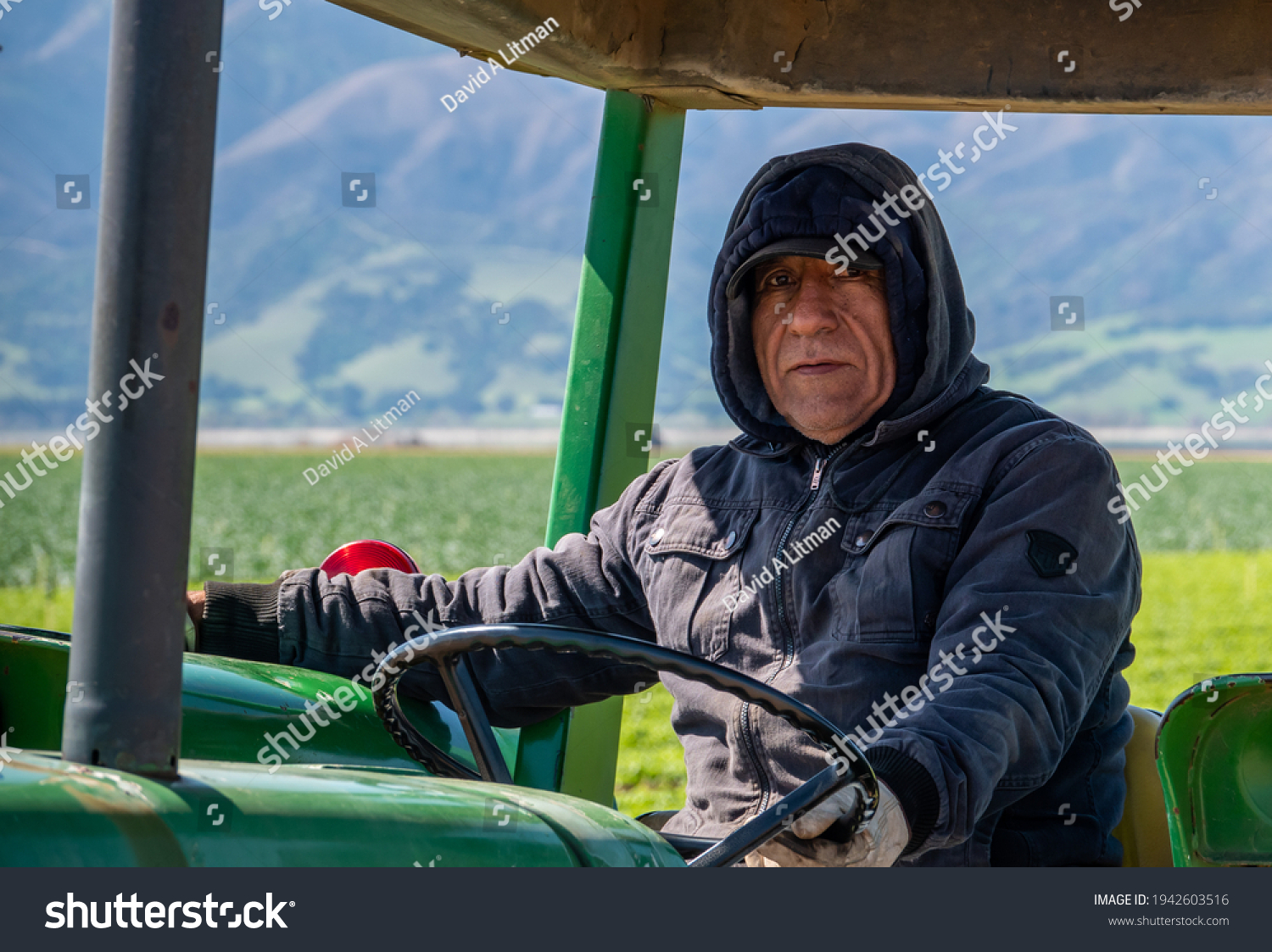 Salinas, California - March 22, 2021: A tractor operator (driver) works the agricultural fields of the Salinas Valley of central California.