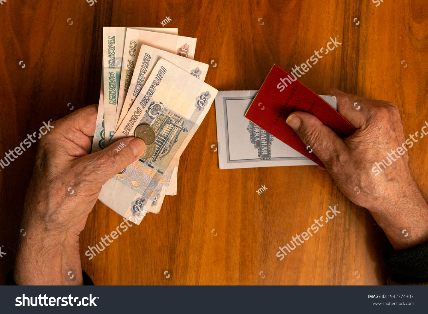 Elderly man holding russian ruble banknotes in one hand and pension certificate with passbook in another. The concept of pension, payment and money savings. #1942774303