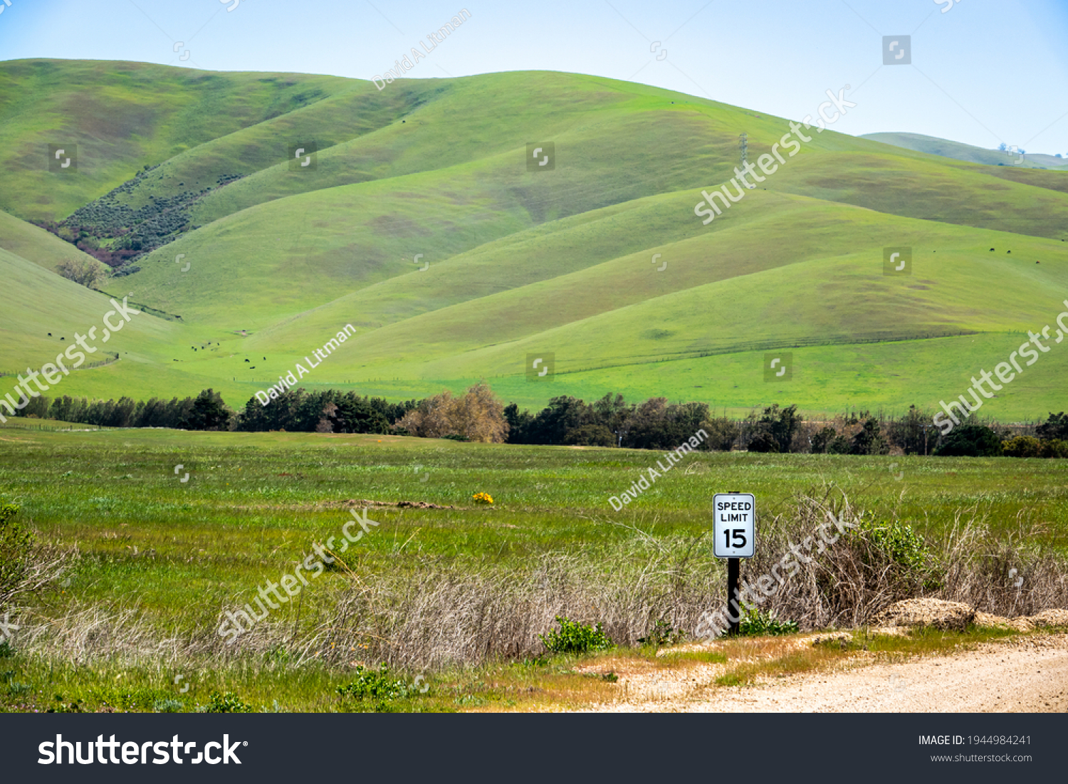 A speed limit sign stands on the side of a rural road in the Salinas Valley of Monterey County in California, with grass covered foothills of the Gabilan Mountains in the background.