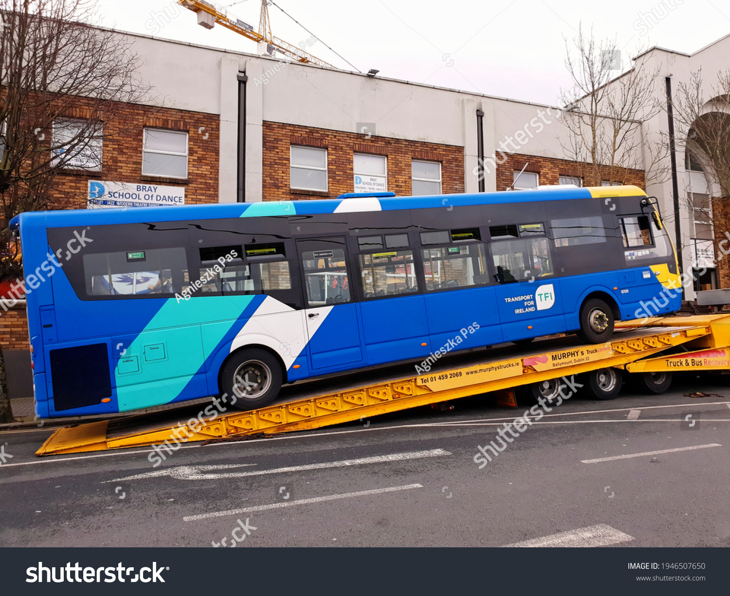 BRAY, CO. WICKLOW, IRELAND - MARCH 15, 2021: Side view of broken bus on a flatbed tow truck. Roadside service.