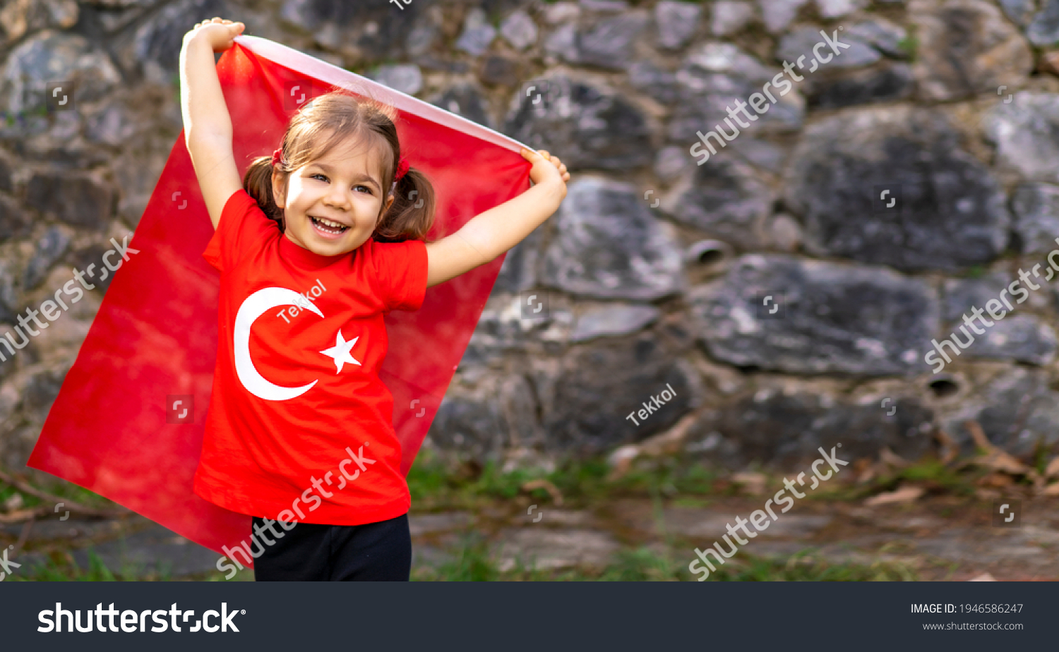 Portrait of happy little kid. Cute baby with Turkish flag t-shirt. Toddler hold Turkish flag in hand. Patriotic holiday. Adorable child celebrates national holidays. Copy space for text. #1946586247