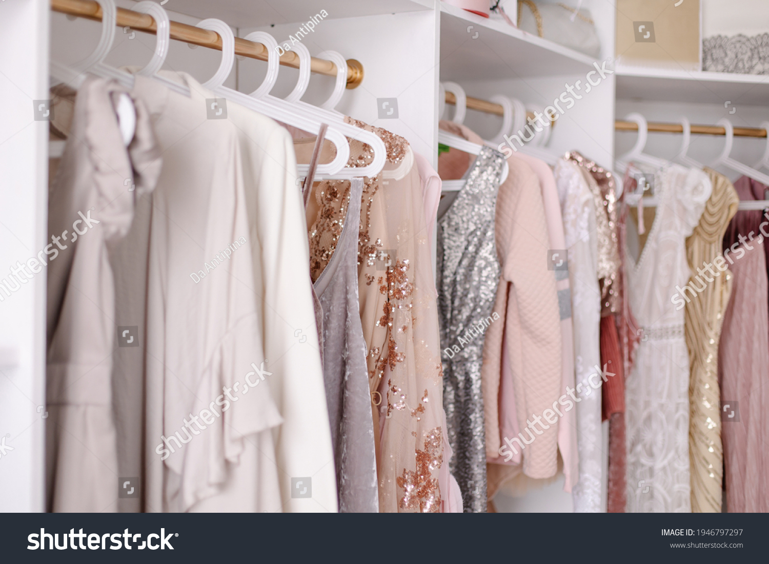 Beautiful female wardrobe. A lot of party dresses hanging on hangers in closet. Vintage clothing rental concept. Women's space. Large selection of various clothes. Small boutique showroom fashion shop #1946797297