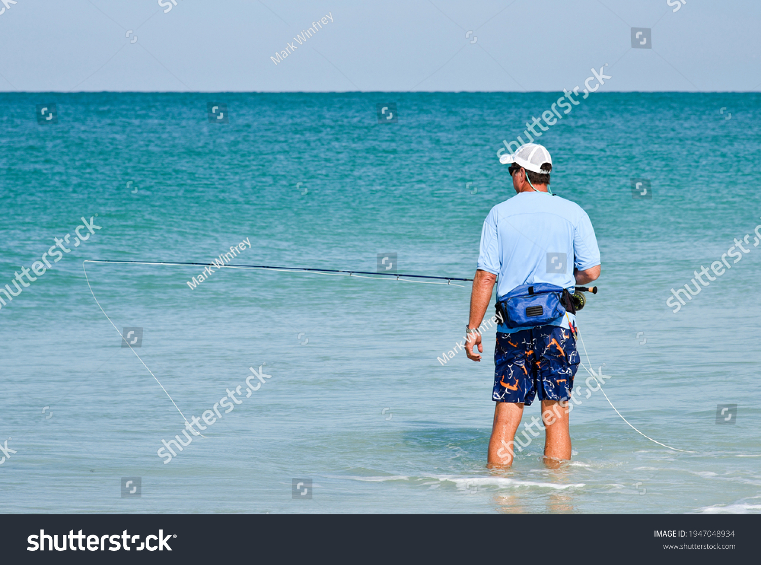 An Unidentified Man Wading in the shallow water of the Gulf of Mexico Fly Fishing on a Beautiful Summer Day.