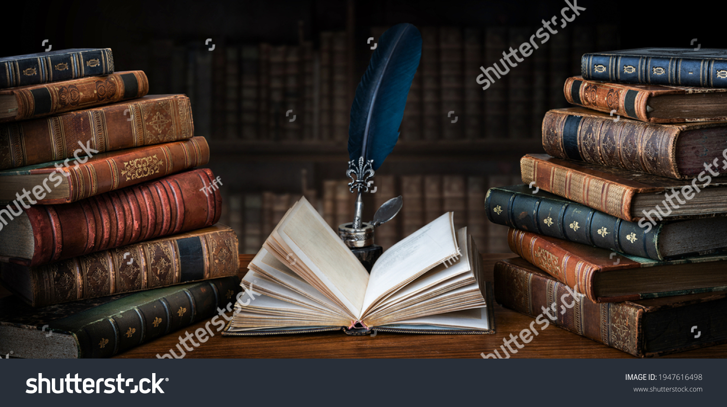 Old books ,quill pen and vintage inkwell on wooden desk in old library. Ancient books historical background. Retro style. Conceptual background on history, education, literature topics. #1947616498