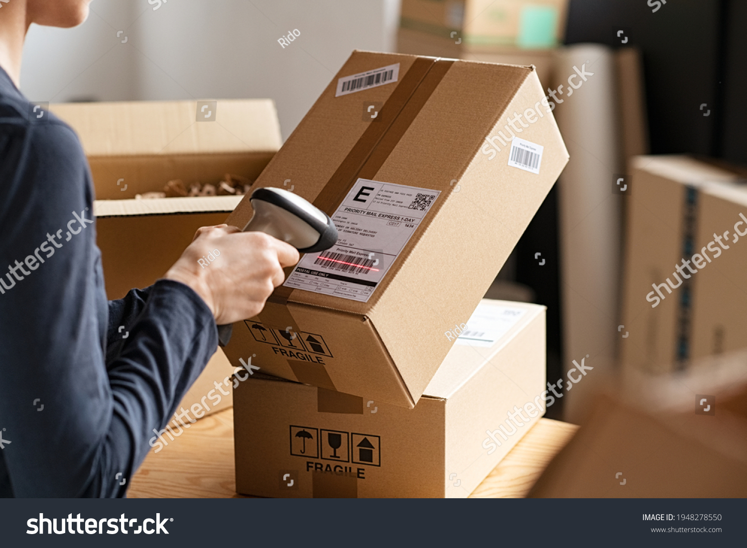 Hands scanning barcode on delivery parcel. Worker scan barcode of cardboard packages before delivery at storage. Woman working in factory warehouse scanning labels on the boxes with barcode scanner. #1948278550
