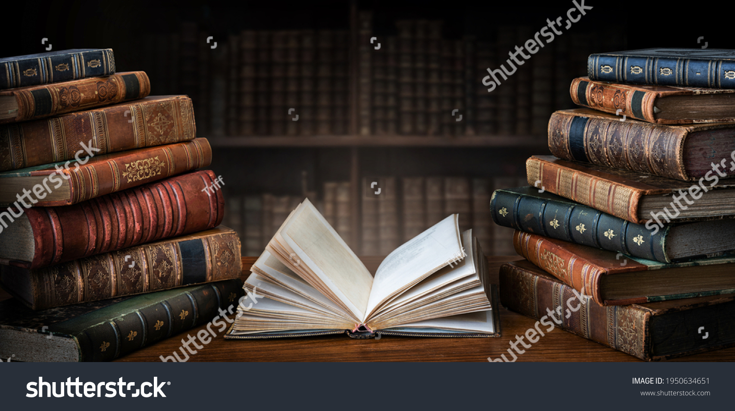 Opened book and stacks of old books on wooden desk in old library. Ancient books historical background. Retro style. Conceptual background on history, education, literature topics. #1950634651