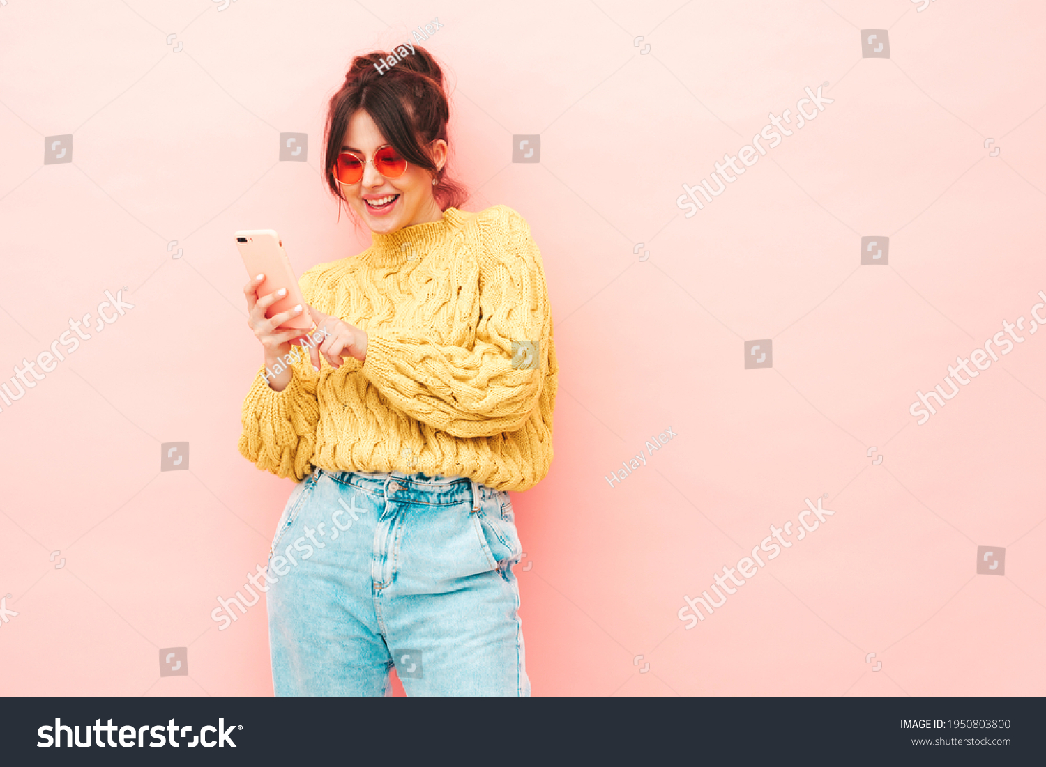 Young beautiful smiling female in trendy summer yellow hipster sweater and jeans.Sexy carefree woman posing near pink wall in studio.Positive model having fun. Looking at smartphone screen, using app #1950803800