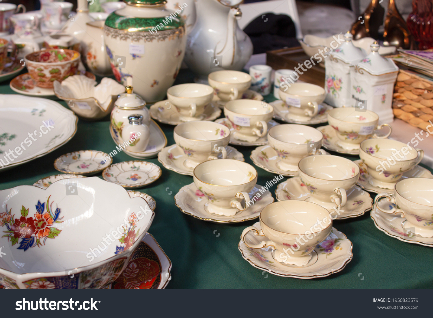 Antiques on flea market or festival - vintage porcelain tea cups, tableware and other vintage things. Collectibles memorabilia and garage sale concept. Selective focus #1950823579