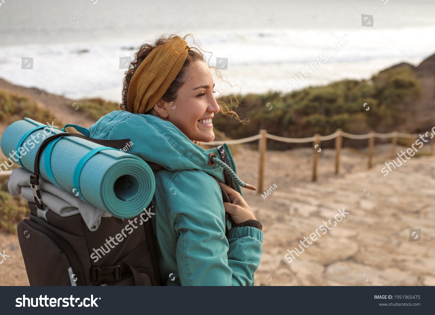 Beautiful young woman walking on a path alonside the coastline - Sportive woman carrying a yoga mat on top of her backpack, on a hike on the mountain #1951965475