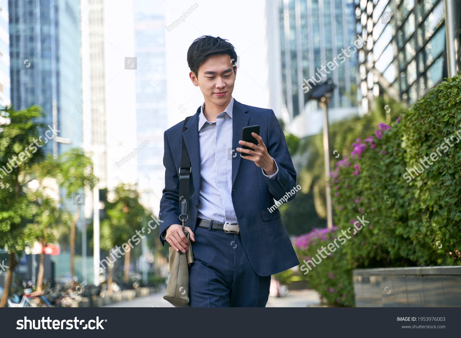 young asian businessman looking at messages on cellphone while walking in the street in downtown of modern city #1953976003