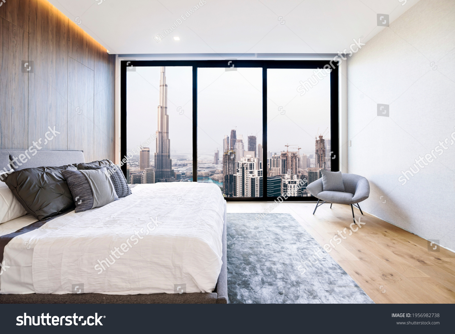 Modern and luxurious bedroom with white ceiling and wood accents with views of Burj Khalifa and downtown Dubai skyline. Condo or Hotel accomodation. #1956982738