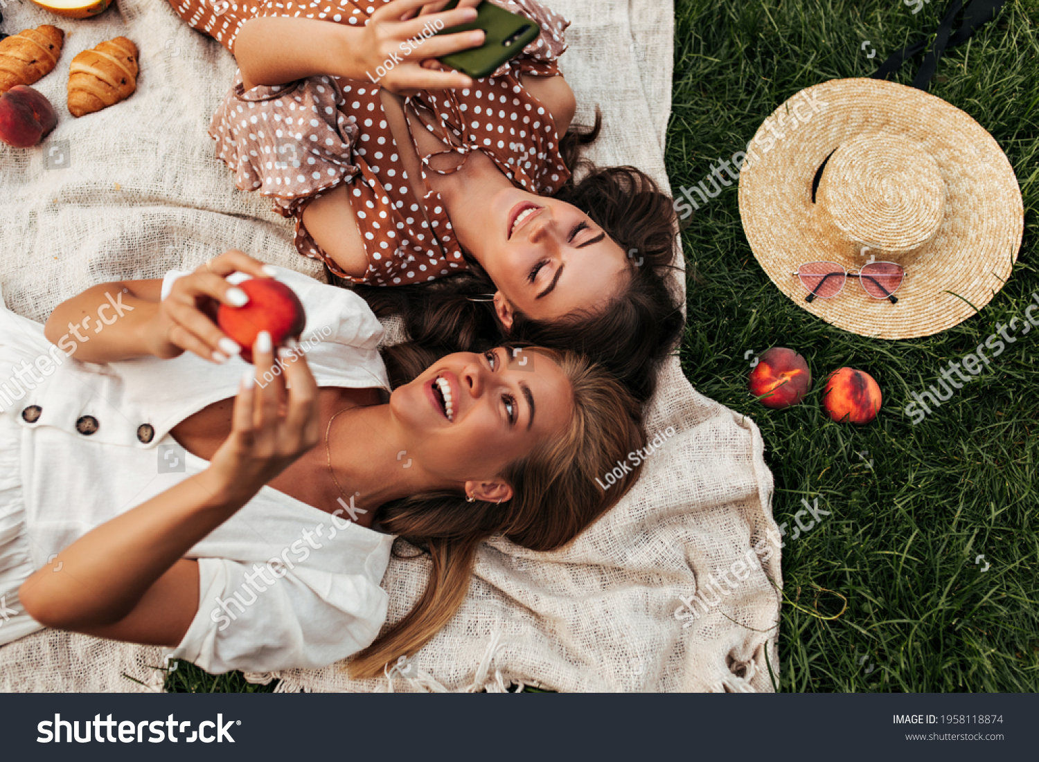 Charming attractive blonde and brunette girls in summer dresses lay on linen rug and have picnic. Cool woman in polka dot dress holds phone. #1958118874