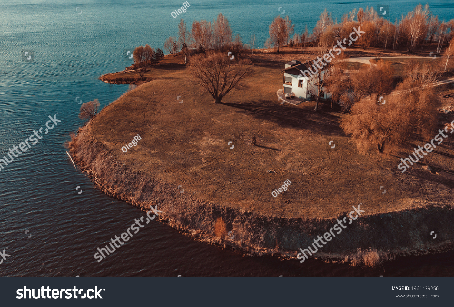 View on red holiday cabin by a lake in Stockholm archipelago, Sweden. Wooden cottage, sauna on shore. Tiny house near the water. Rocky small island, islet in water. Buildings surrounded by green trees #1961439256