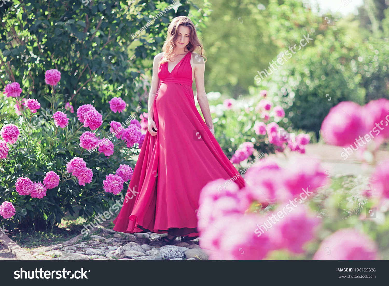 Pregnant woman in blooming garden of peony stock photo for Gardening while pregnant