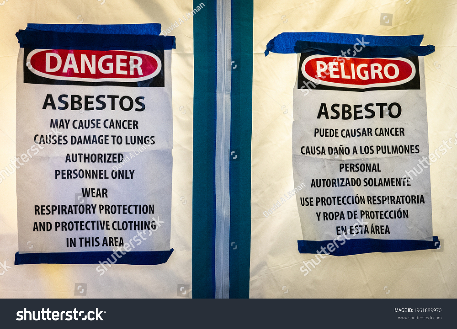 Bilingual signs in English and Spanish warns of the risk of lung cancer (and mesothelioma) from exposure to asbestos during remodeling of an old kitchen.