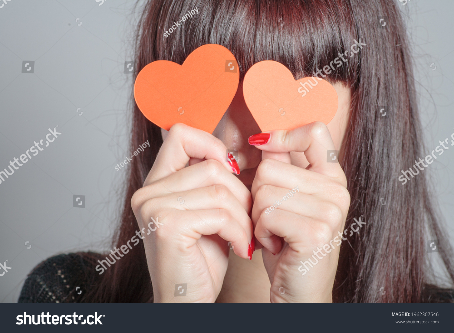 A girl covering her eyes with paper hearts, she is having fun and expressing her love vision