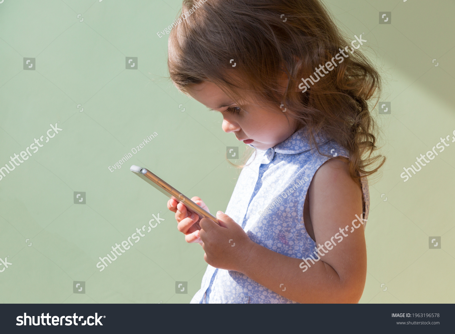 beautiful  toddler girl playing with smartphone. the girl is isolated on green wall. Technology and lifestyle concept