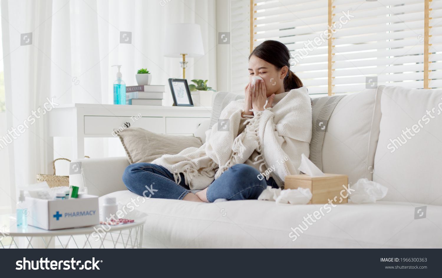Sick young asian woman sitting under the blanket on sofa and sneeze with tissue paper at home. Female blowing nose, coughing or sneezing in tissue at home, suffering from flu. Cold and fever concept #1966300363