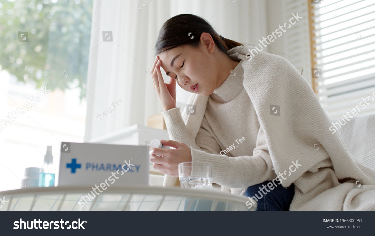 Sick asian woman sit under blanket acute severe headache on sofa at home. Female hold or check drug medicine capsule at home, suffer from flu. Cold or fever side effect after Covid19 vaccine shot. #1966300951