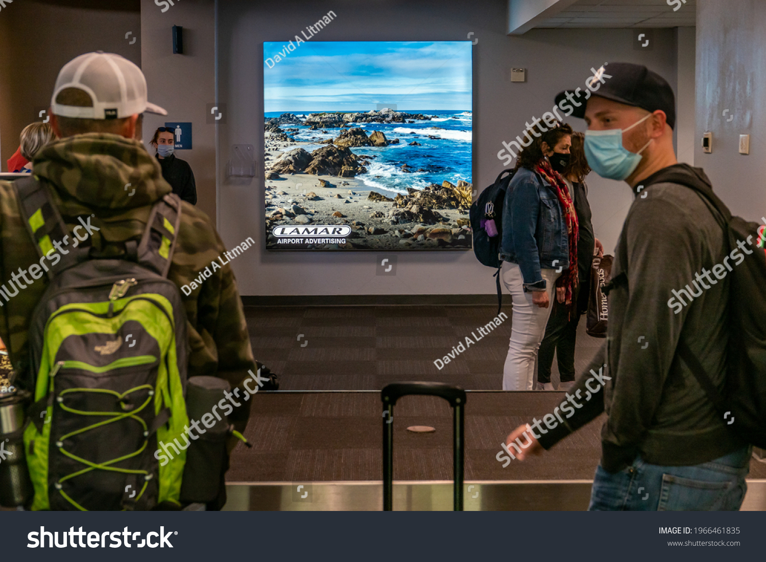 Monterey, California - May 1, 2021: A photograph of Asilomar Beach by Shutterstock photographer David A Litman is on display at the Monterey Airport baggage claim area.