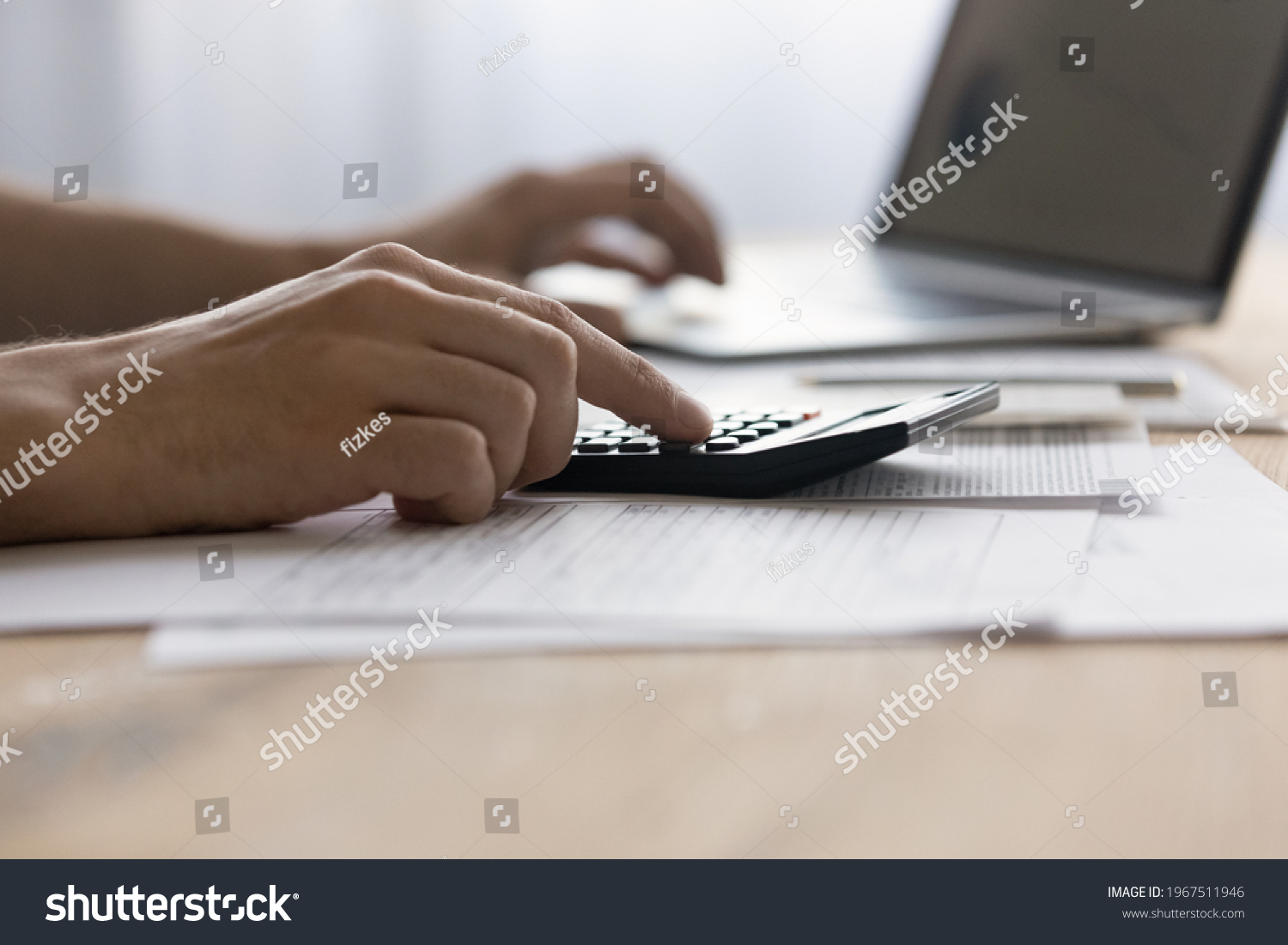Close up man laptop and calculator, managing finances or planning budget, businessman calculating corporate bills, expenses, browsing online banking service, sitting at table with financial documents #1967511946