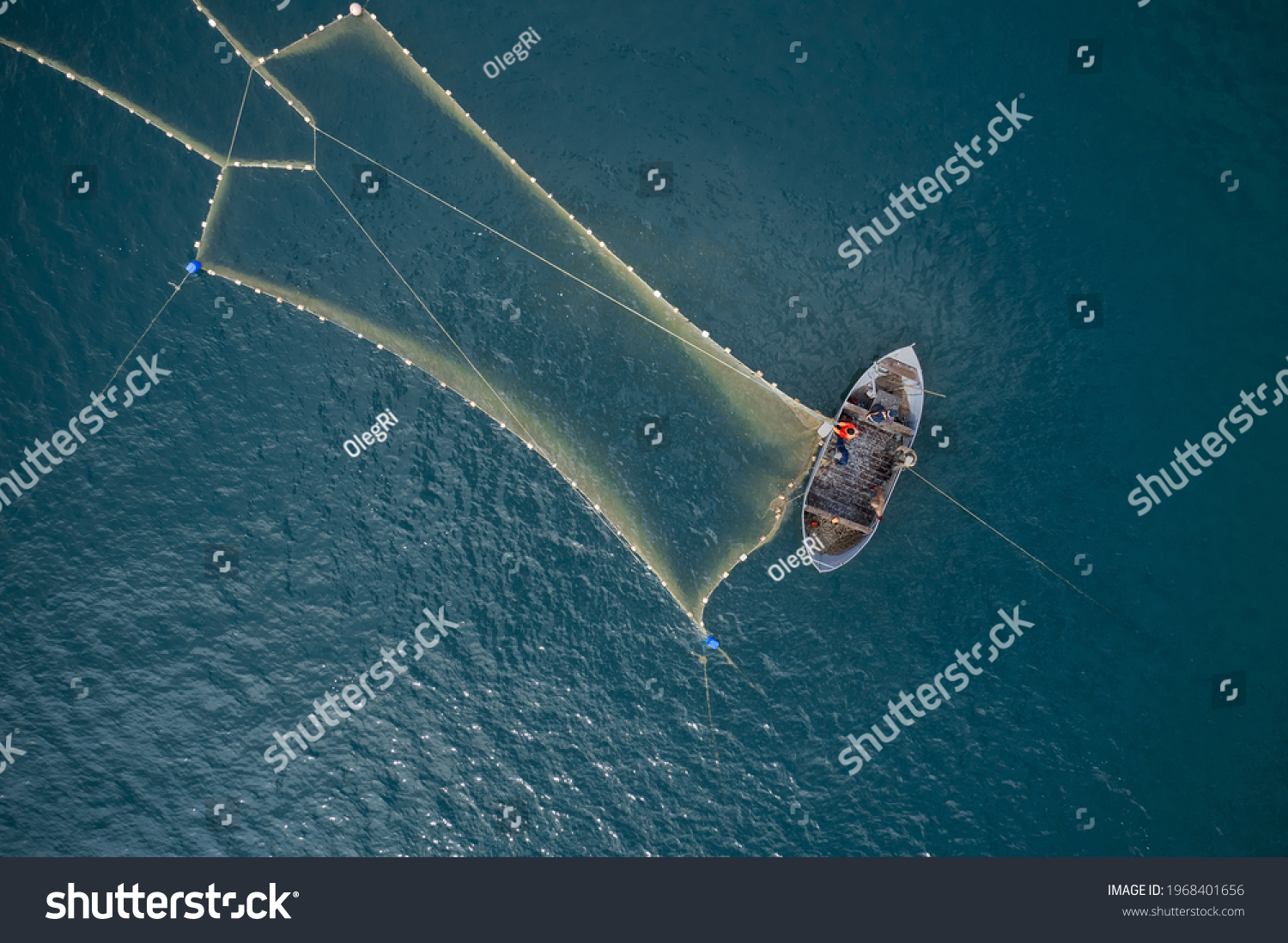 Vintage wooden boat in coral sea. Boat drone photo. A fisherman on a fishing boat is casting a net for catching fish. #1968401656