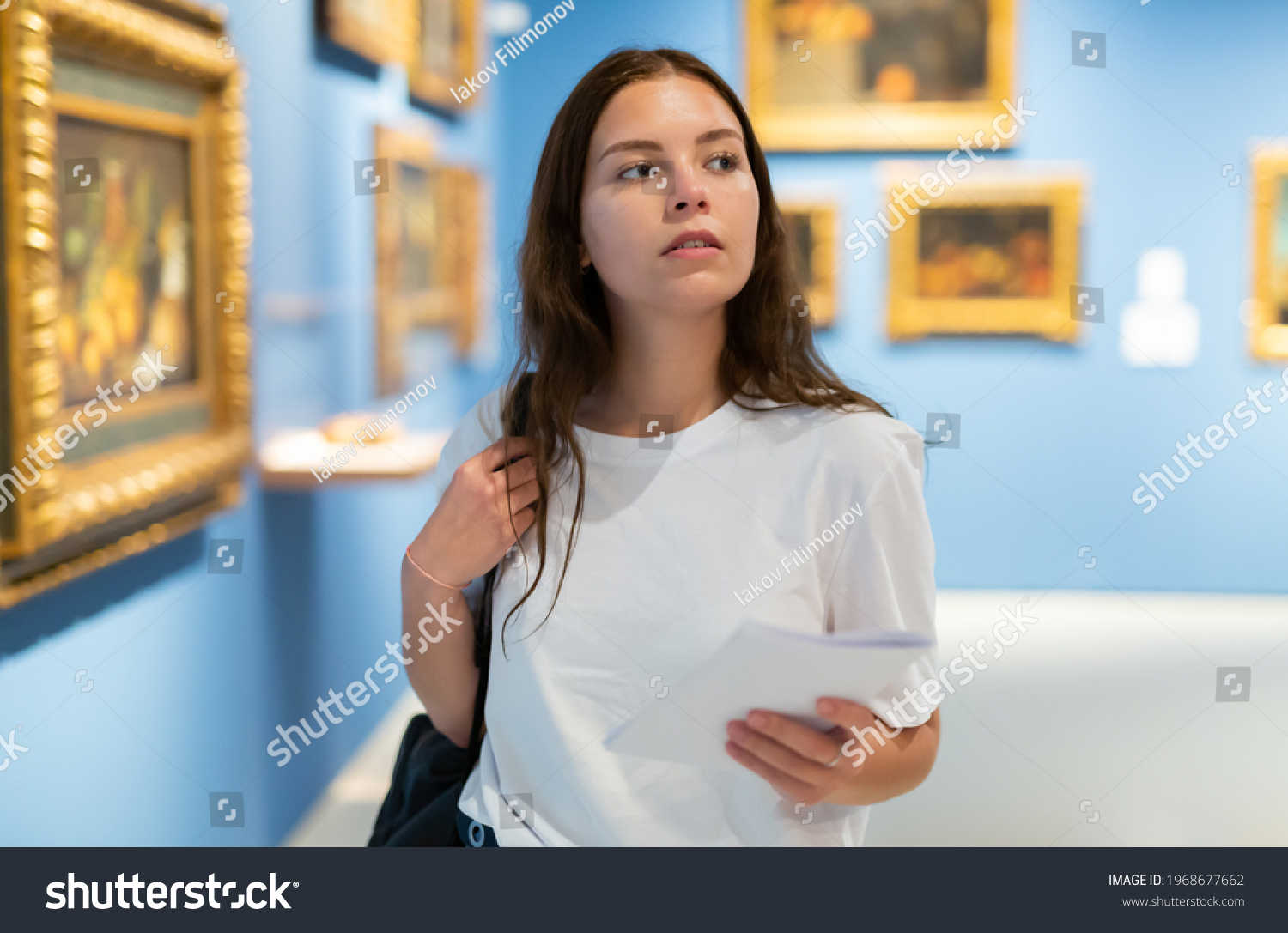 Focused young girl visitor holds a booklet with an exhibition program while admiring the paintings in the museum #1968677662
