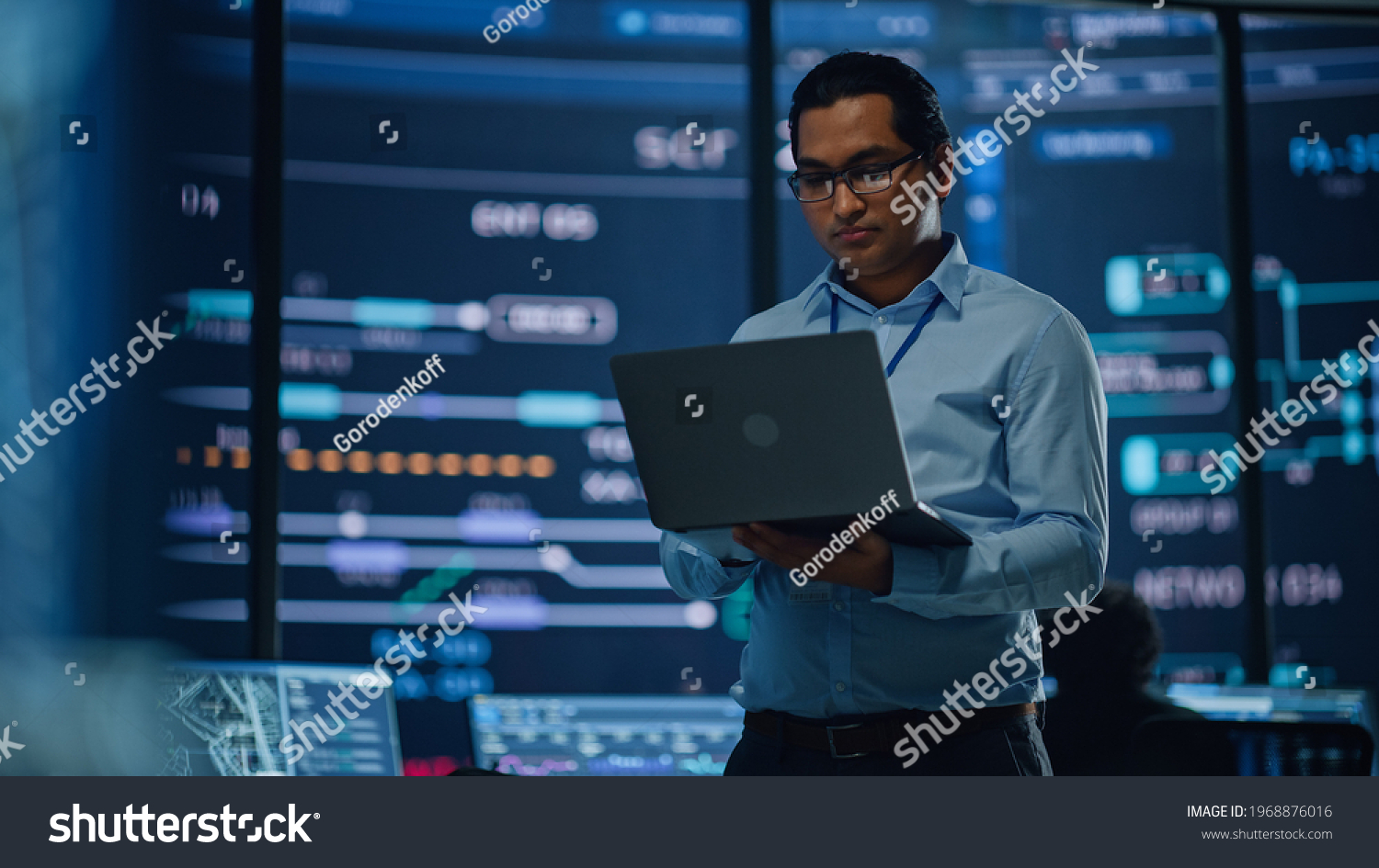 Young Multiethnic Male Government Employee Uses Laptop Computer in System Control Monitoring Center. In the Background His Coworkers at Their Workspaces with Many Displays Showing Technical Data. #1968876016
