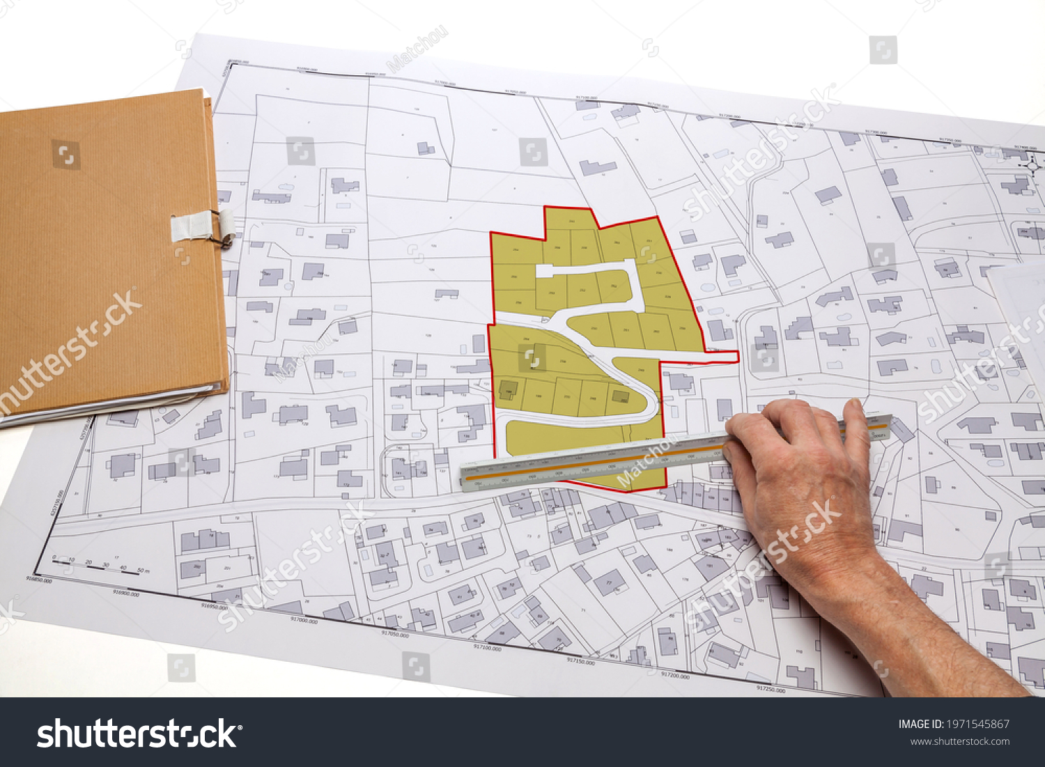 Town planning and land use planning - hand holding a measuring ruler in front of a zoning of plots, on a cadastral plan placed on a desk #1971545867