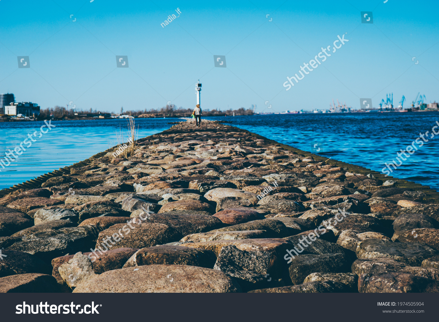 clear blue sky on the pier large stones in the foreground . High quality photo #1974505904