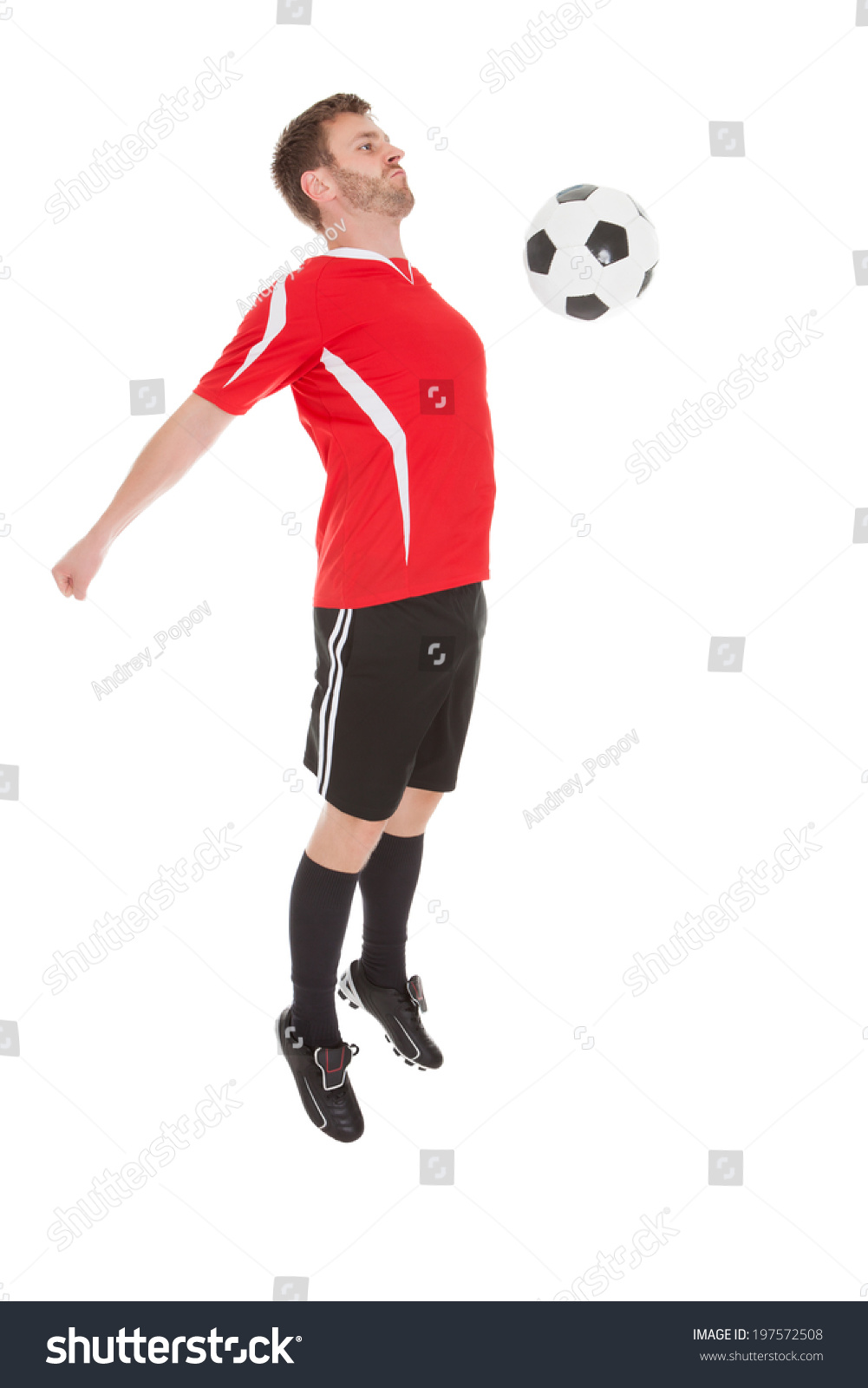 2c42bfc7f football player kicking controlling ball with chest isolated on white  background wearing red jersey and socks and black shorts on green grass  pitch