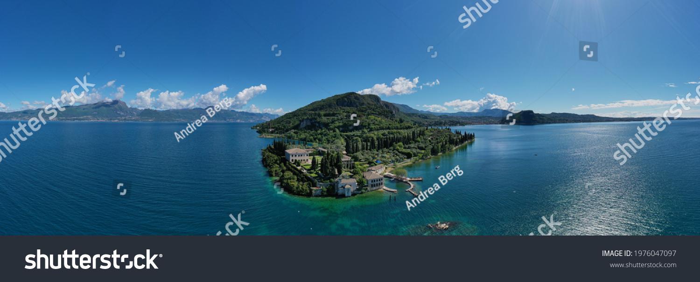 Panorama of punta san vigilio.  Aerial view of Parco Baia delle Sirene, Lake Garda, Italy. Top view of baia delle sirene on the coastline of Lake Garda. Baia delle Sirene on the coastline. #1976047097