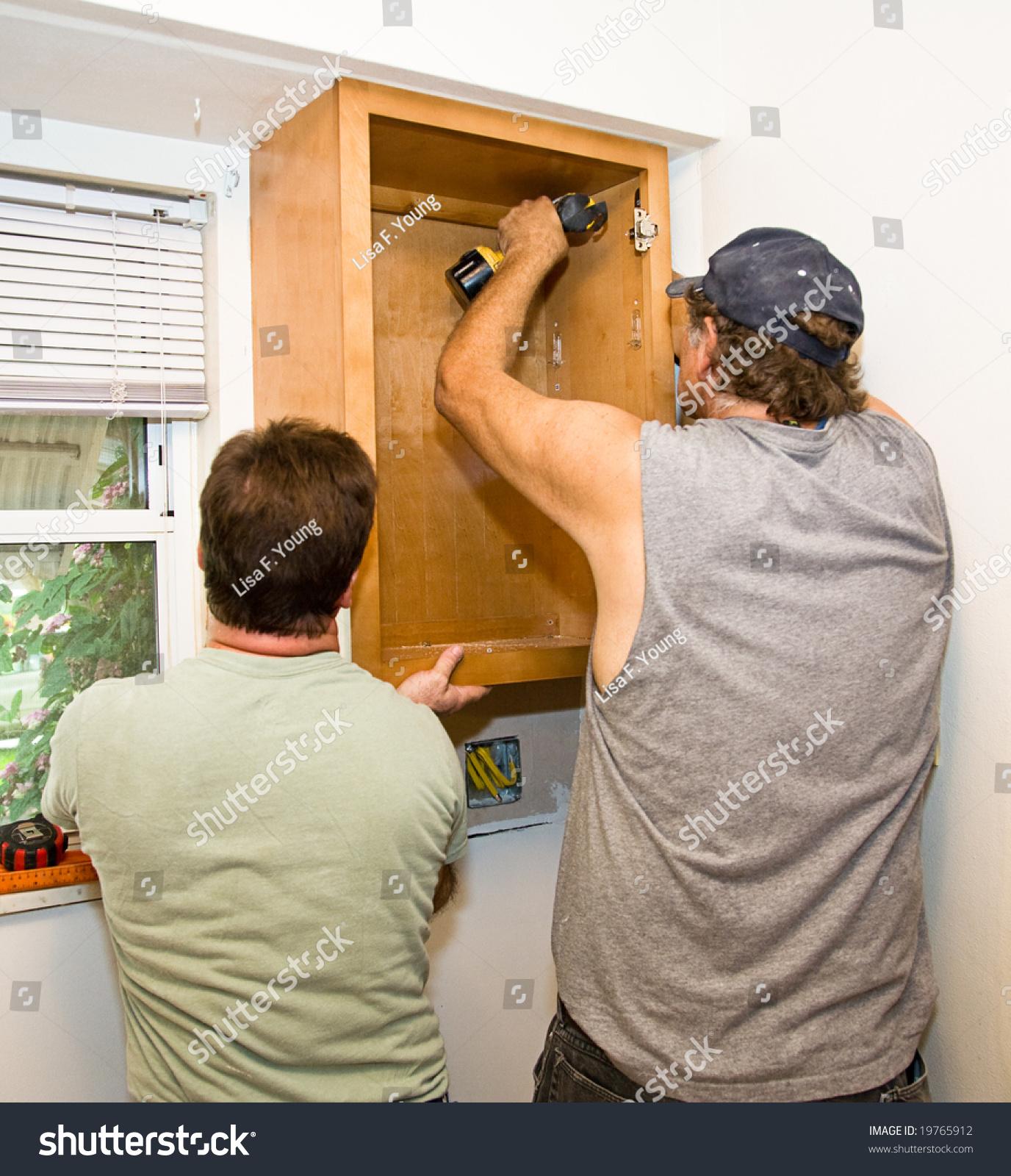 Carpenter helper installing kitchen cabinets together for Carpenter for kitchen cabinets