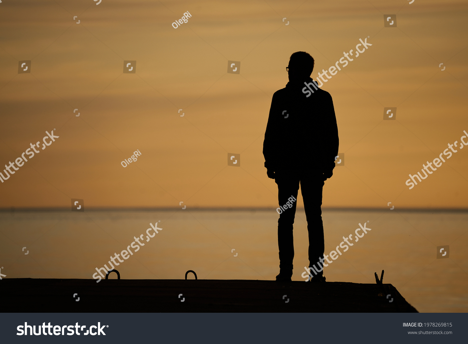 man standing on rock looking straight. Nature and beauty concept. Orange sundown. silhouette at sunset #1978269815