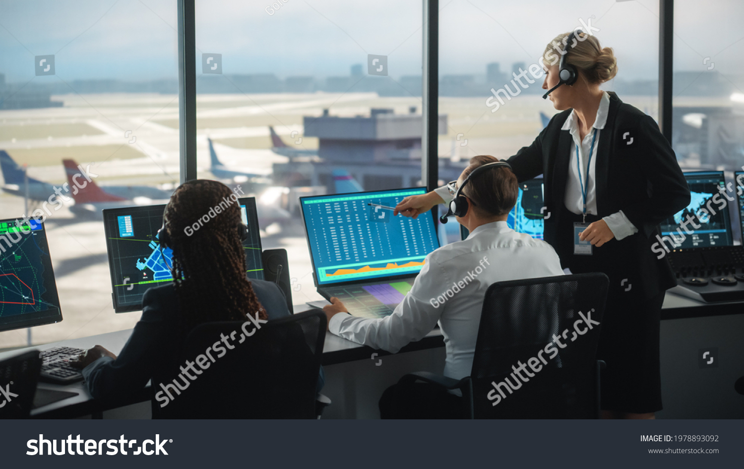 Female and Male Air Traffic Controllers with Headsets Talk in Airport Tower. Office Room is Full of Desktop Computer Displays with Navigation Screens, Airplane Departure and Arrival Data for the Team. #1978893092