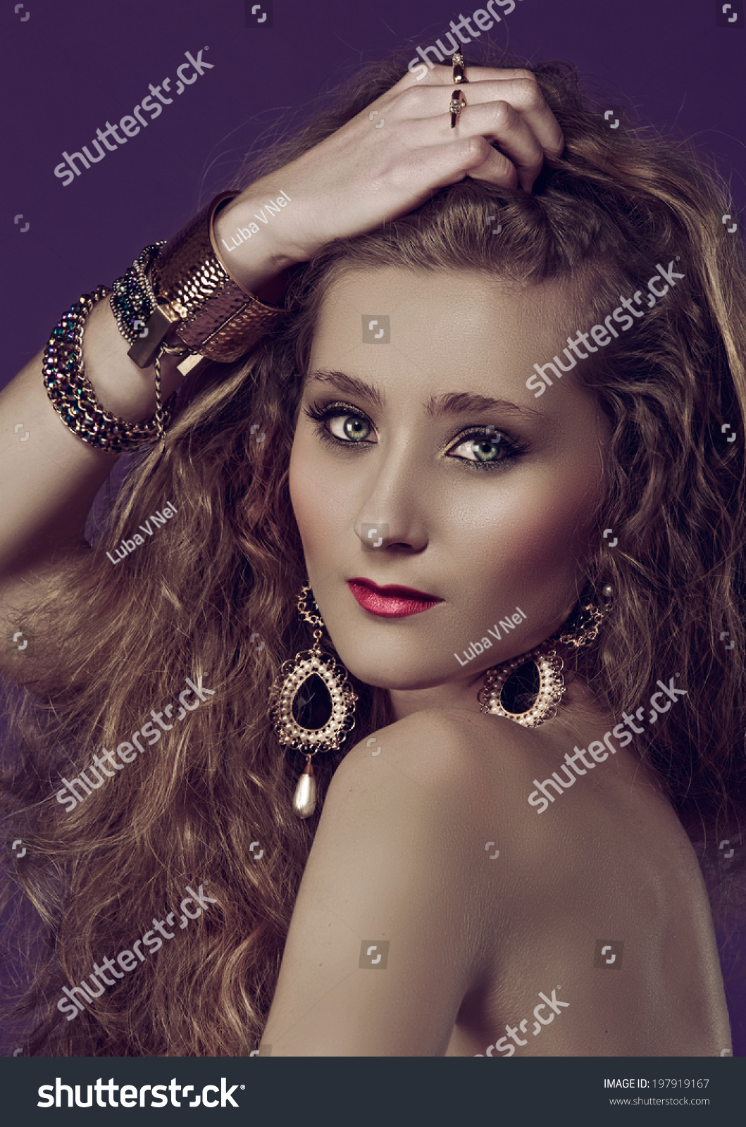 Portrait Of A Young Beautiful Woman With Long Blond Curly Hair Wearing Pearl  Earrings And Gold